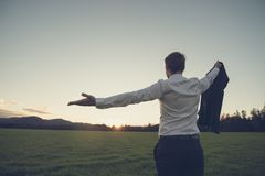 Businessman standing in green meadow looking towards the sunset royalty free stock photos