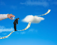 Businessman standing on growing money trend with hand winding i. N blue sky background stock photos