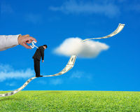 Businessman standing on growing money trend with hand winding. In meadow, blue sky background stock images