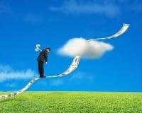 Businessman standing on growing money trend with meadow and sky. Businessman standing on growing money trend with meadow and blue sky background stock photo