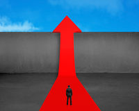 Businessman standing on growing red arrow with wall and sky Royalty Free Stock Photo