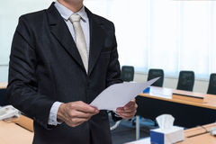 Businessman standing hand holding paper on meeting room background.  Stock Photos