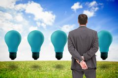 Businessman standing with hands behind back looking at blue light bulbs Stock Images