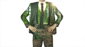Businessman standing with hands on hips with forest overlay stock video