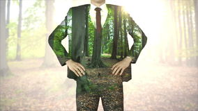 Businessman standing with hands on hips with forest overlay stock video footage