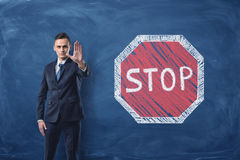Businessman standing with his arm forward and traffic-sign `Stop` painted on blackboard behind him Royalty Free Stock Image