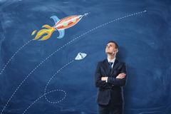 A businessman standing with his arms folded on the dark blue background, he is looking up at the pictures of the rocket. And the UFO drawn on the wall. Long stock images