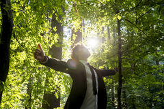 Businessman standing with his arms outspread in woodland royalty free stock photos