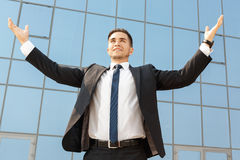 Businessman standing with his arms raised up Stock Photos