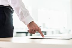 Businessman standing at his desk pointing to a document, application or contract holding a pen stock photos