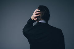 Businessman standing with his hand to his head. View from behind of a stylish businessman standing with his hand to his head as he scratches it in perplexity or Royalty Free Stock Photography