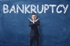 Businessman standing with his hands like cross sign and word `Bankruptcy` written on blackboard behind him royalty free stock photos