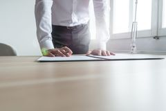 Businessman standing at his office desk leaning to sign a contra royalty free stock photography