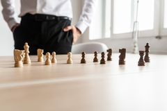 Businessman standing at his office desk looking at black and white chess pieces arranged on the wooden desk. With copy space on stock photo
