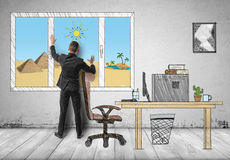 Businessman standing in his office in front of the window with pyramids and sands behind it Royalty Free Stock Photo