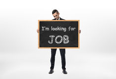 Businessman standing and holding blackboard with words `I`m looking for job` written on it Stock Photography