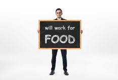 Businessman standing and holding blackboard with words `will work for food` written on it Royalty Free Stock Images