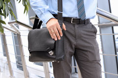 Businessman standing  and holding  a  leather briefcase on his s Royalty Free Stock Image