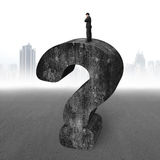Businessman standing on huge 3D concrete question mark cityscape Stock Photo