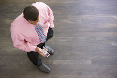 Businessman standing indoors looking at phone. Looking down from the camera Stock Image
