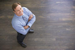 Businessman standing indoors smiling. Looking up at camera Royalty Free Stock Images