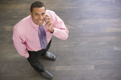 Businessman standing indoors using cellular phone Stock Photos