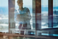 Businessman standing inside office building and using laptop Stock Photos