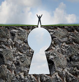 Businessman Standing On Keyhole. Mountain cliff as a person with arms up in victory on top of a rock mountain shaped as a key hole business and finance symbol Stock Image