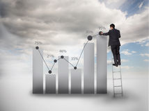 Businessman standing on a ladder drawing a chart Stock Photo