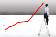Businessman standing on ladder drawing diagrams royalty free stock photo