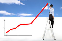 Businessman standing on ladder drawing global diagrams stock photos