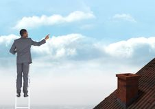 Businessman standing on ladder near roof. Digital composite of Businessman standing on ladder near roof Stock Photography