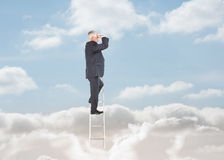 Businessman standing on a ladder over clouds Royalty Free Stock Photography
