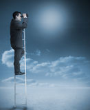 Businessman standing on ladder over clouds Stock Photography