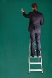 Businessman Standing On Ladder Writing On Chalkboard. Rear View Of A Businessman Standing On Ladder Writing On Chalkboard Royalty Free Stock Photography