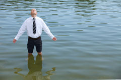 Businessman standing in lake, eyes closed Royalty Free Stock Images