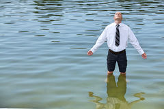 Businessman standing in lake, eyes closed stock image