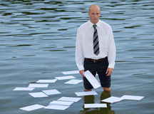 businessman standing in lake with papers on water Stock Photo