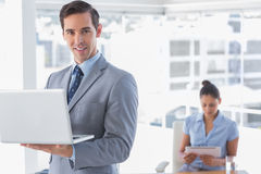 Businessman standing with laptop and smiling at camera. With women working behind him Stock Image