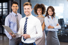 Businessman standing with a laptop and team standing in background Stock Image