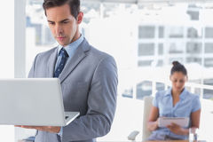Businessman standing with laptop. With women working behind him Royalty Free Stock Photo