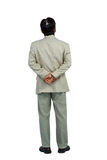 Businessman standing and looking with hands behind back Stock Photography