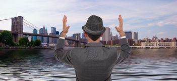 Businessman standing looking at New York City's skyline. With his arms up Stock Photos