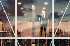Businessman standing and looking out the window of the office at Stock Images