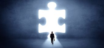 Businessman standing in front of a big puzzle piece stock image