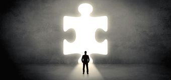 Businessman standing in front of a big puzzle piece. Businessman standing and looking to a big puzzle piecen royalty free stock images