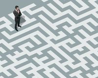 Businessman standing on a maze and searching for a way out. Solution and business strategy concept stock photos
