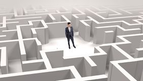 Businessman standing in a middle of a maze stock photo