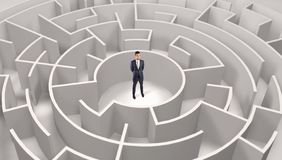 Businessman standing in a middle of a round maze royalty free stock photos