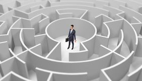 Businessman standing in a middle of a round maze stock image